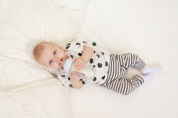 Baby 8 months old lying on the bed in pajamas and drinking milk from a bottle, baby food concept