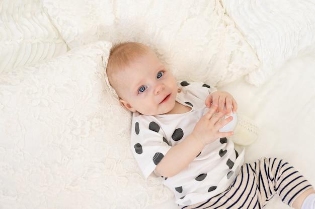 赤ちゃんのボトル、牛乳、ベビーフードのコンセプト、赤ちゃんのミルクを吸う、テキストの場所でパジャマで自宅のベッドに横になっている8ヶ月の赤ちゃん