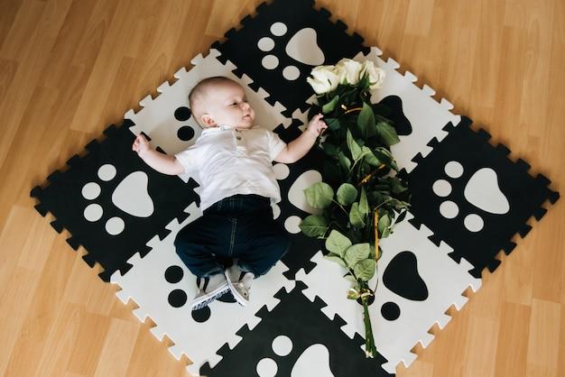 赤ちゃん、小さな紳士は、休日に男への贈り物、バラの花束で敷物を開発しています
