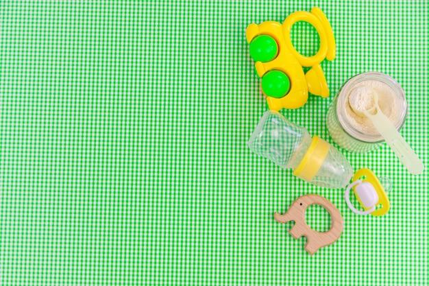 녹색 배경에 아기 액세서리와 음식. 선택적 초점.아기