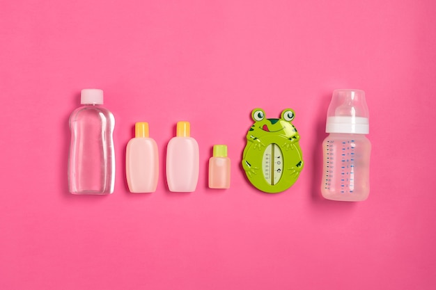 Baby accessories for bath with frog on pink background. top view. copy space. still life. flat lay