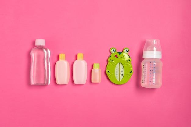 Детские аксессуары для ванны с лягушкой на розовом фоне. вид сверху. скопируйте пространство. натюрморт. плоская планировка