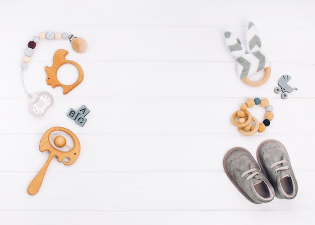 Baby accessories on white wooden background with copyspace