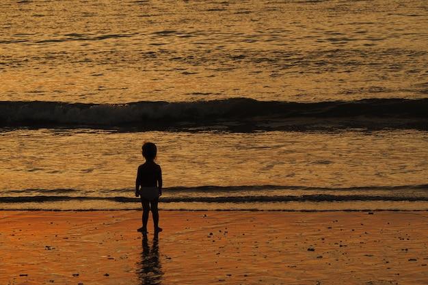 一人で、日没で海を見ている赤ちゃん