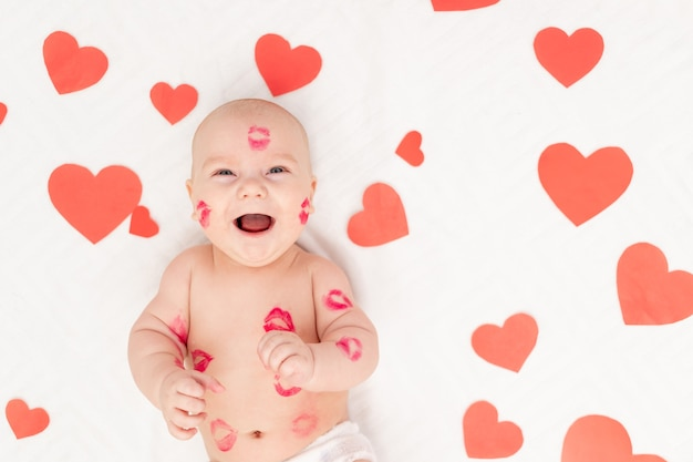 Baby among hearts and with kisses from red lipstick, the concept of love and valentine's day