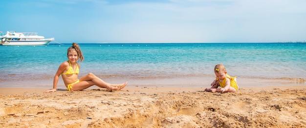 海の近くのビーチで赤ちゃんと姉