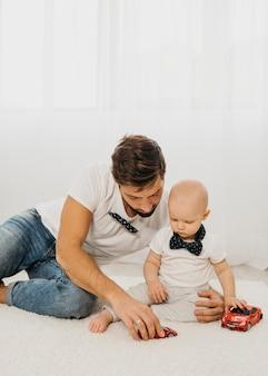 家で一緒に遊ぶ赤ちゃんと父親