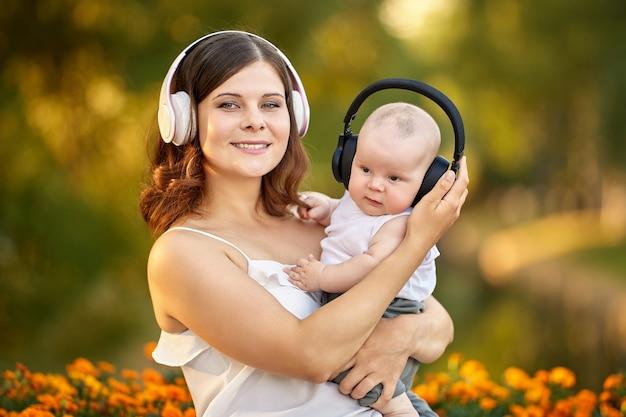 赤ちゃんと彼の母親は自然の中でワイヤレスヘッドフォンを介して音楽を聴きます