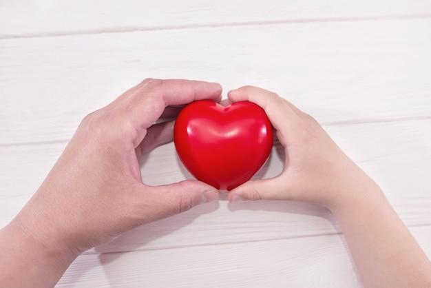 Ребенок и мама за руки держат красное сердце сердечное страхование здоровья пожертвование органов волонтерская благотворительная организация социальная ответственность за социальную ответственность