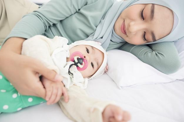 ベッドで赤ちゃんと母親、幸せな愛情のある家族