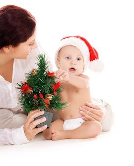 白い壁の上のクリスマスプレゼントと赤ちゃんと母親