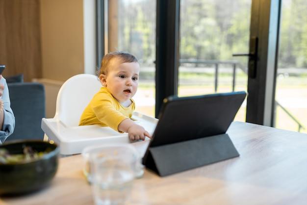 自宅での昼食時にデジタルガジェットで忙しい赤ちゃんと両親