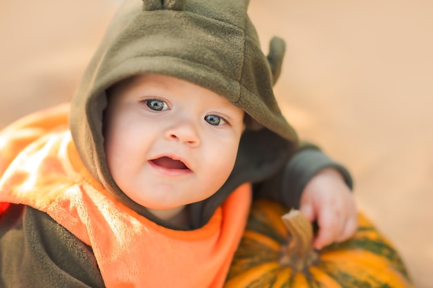 Младенец и тыквы в природе. забавный малыш на хэллоуин и тыквы