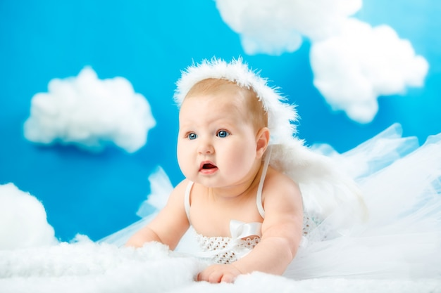 The baby as the angel soaring in clouds.
