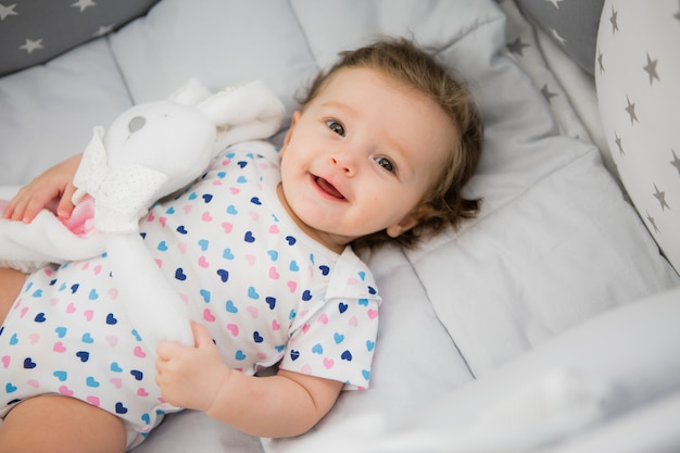 Baby in a baby bed on a light background