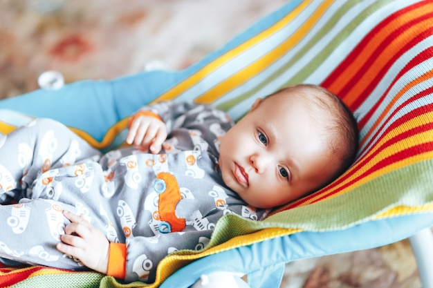 Baby in baby chaise deck-chair colourful home