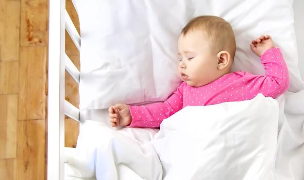 아기 아기는 침대에서 잔다. 선택적 초점.