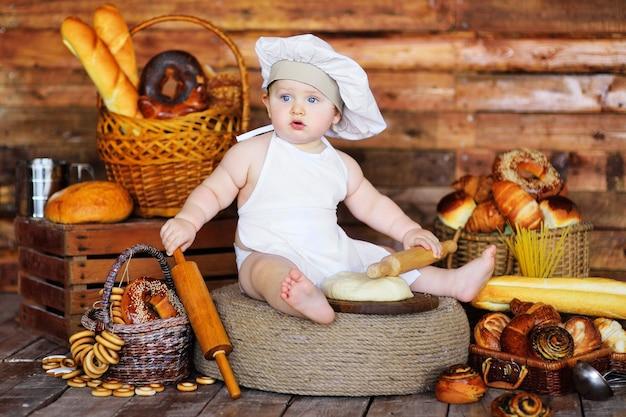 シェフの帽子とエプロンを身に着けた男の子の赤ちゃんが、ベーカリー製品の背景に木製の麺棒で生の生地を広げます