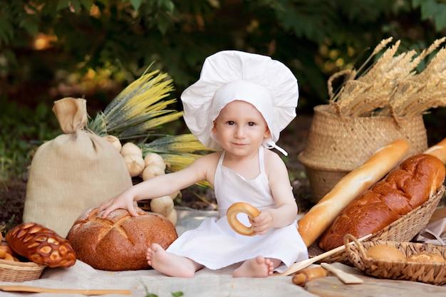 赤ちゃんのパン屋は自然の中で調理します。ピクニックの少年は白いエプロンと帽子でパンとベーグルを食べる