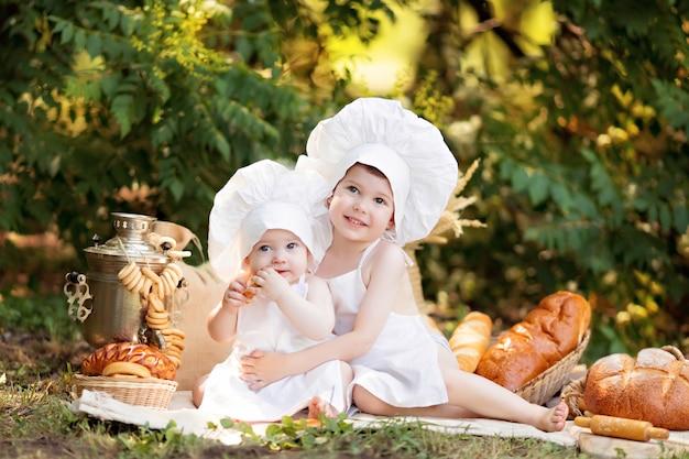 日当たりの良い夏の日にピクニックに赤ちゃんパン屋が白いエプロンでパンとベーグルを食べ、自然に帽子をかぶる