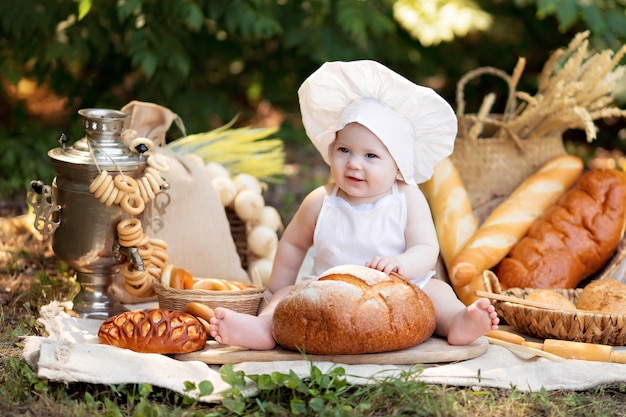 Baby baker on a picnic eats bread and bagels in white apron and hat on nature on a sunny summer day