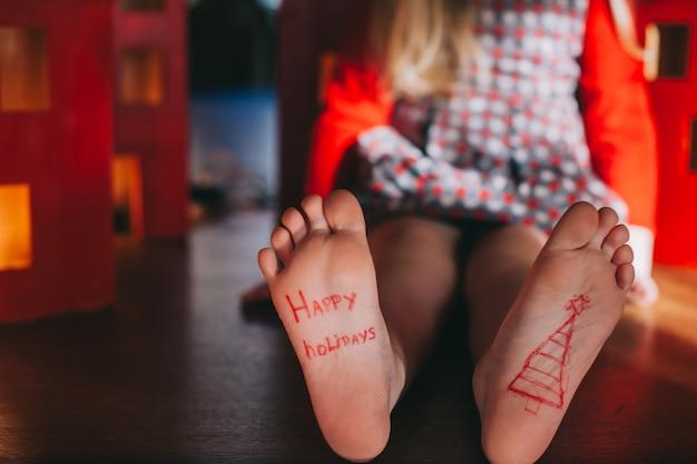 木製の床に赤ちゃんの裸足。クリスマスのお祝いのコンセプト