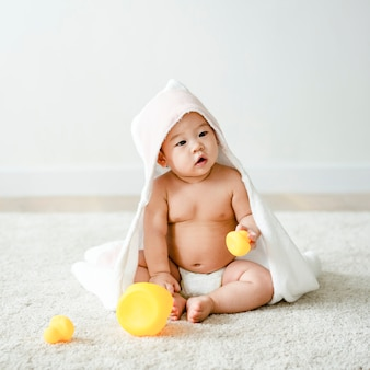 Baby in a bath towel with rubber ducks