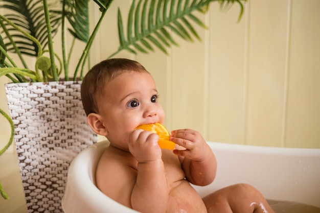 Baby bathes in a bath and eats an orange on a wooden wall