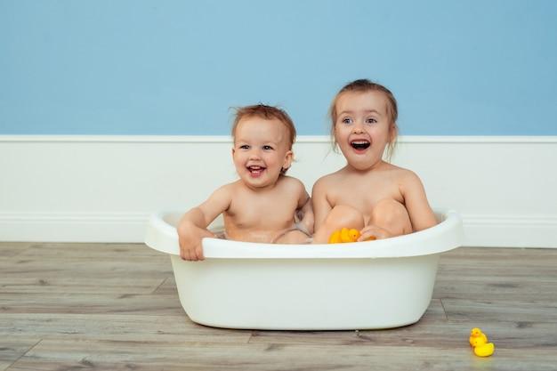 Детское купание и гигиена. забота о маленьких детях. две веселые сестры купаются в белой детской ванночке и играют среди мыльной пены