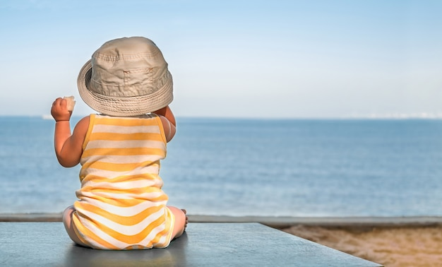 Baby on the beach table sits in the hat and looks at the sea