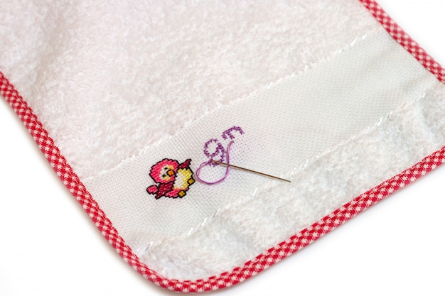 Baby bib with cross-stitched embroidery