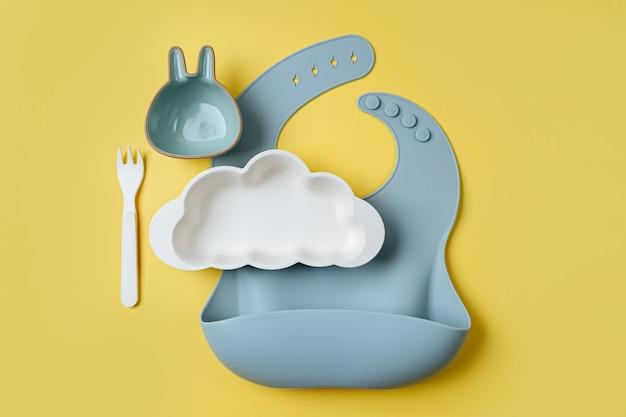 노란색 배경에 구름 모양의 아기 턱받이와 접시. 봉사하는 아기. 어린이 메뉴, 영양 및 수유의 개념