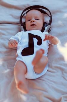 Baby in big headphones lying on bed