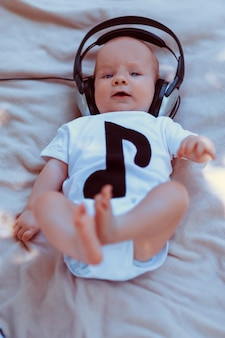 Baby in big headphones lying on bed