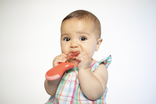 Baby biting into a toy in multicolored dress, isolated on white with copy space