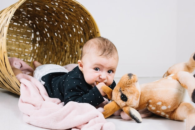 Baby biting toy and looking at camera
