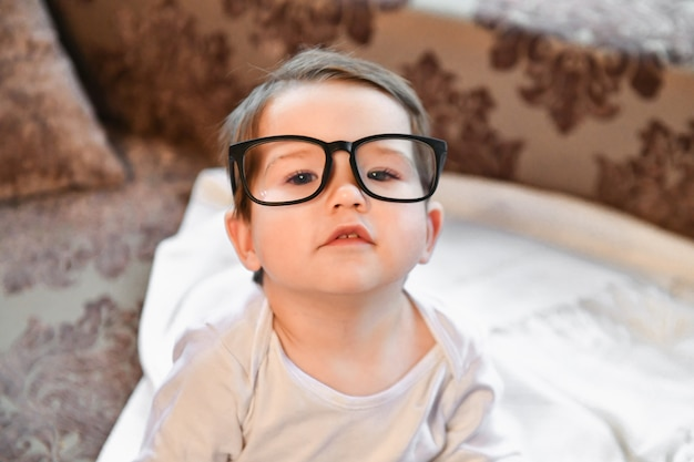 Baby in black glasses. poor vision in a child.