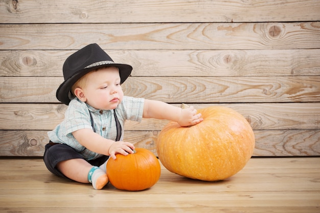 Baby in black hat with pumpkins on wooden surface