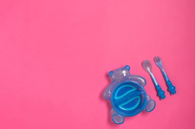Детская синяя тарелка с ложкой и вилкой, изолированные на розовом виде сверху