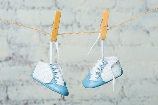 흰색 벽돌 벽에 밧줄에 아기 파란색 신발.