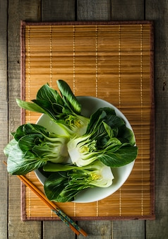 Baby bok choi on bamboo placemat on rustic background