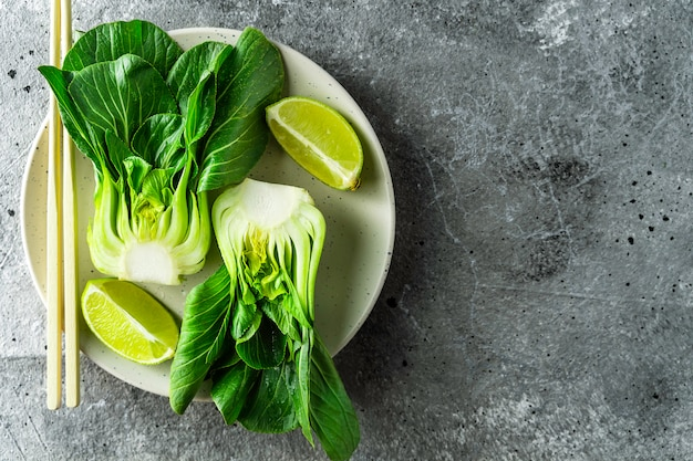 Baby bok choi halves, limes, chopsticks on gray background