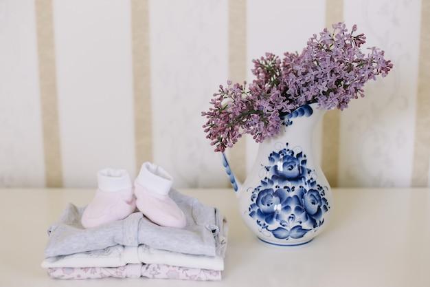 Детские пинетки и одежда с букетом сиреневых цветов на фоне