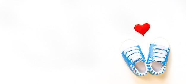 Детские пинетки и сердце изолируют на белом фоне. выборочный фокус.
