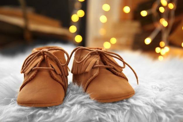 ふわふわのカーペットの上にベビーブーツ。クリスマスのコンセプト