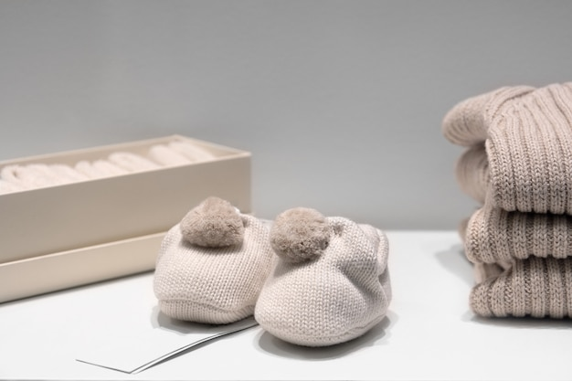 Baby booties, sweaters and socks made of natural beige fabrics lie on the table.