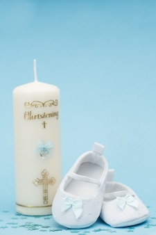 Baby booties with blue ribbon and christening candle