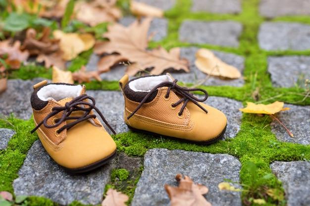 秋の公園でベビーブーツ。屋外の黄色の葉を持つ子供靴。
