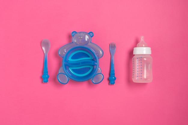 Детская бутылочка и синяя тарелка с ложкой и вилкой, изолированные на розовом виде сверху