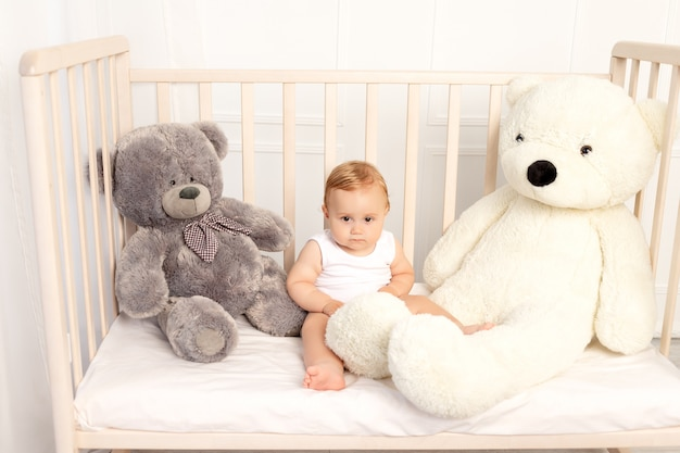 Baby boy 1 year old sitting in a crib with large teddy bears, baby in the nursery